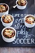 Französische Zwiebelsuppe in kleinen Formen auf Schieferplatte für einen Fussballabend