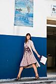 Frau im gemusterten Seidenkleid und Trenchcoat vor blauer Wand