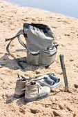Gepäck und Schuhe im Sand an Wasserstelle, Sambia, Afrika