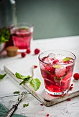 Raspberry lemonade with fresh raspberries, mint and ice cubes