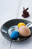 Colourful eggs on a plate with a chocolate bunny