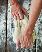 A baker kneading dough on a floured wooden surface