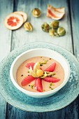A smoothie bowl wit grapefruit, physalis and pistachios