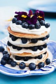 A stack of pancakes with blueberries and pansies