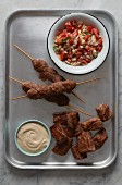 Minced meat kebabs and diced meat with hummus and salsa