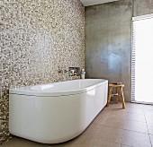 Freistehende, weiße Badewanne an Mosaikfliesenwand in minimalistischem Bad mit Betonwand