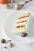 A slice of a speckled Easter cake with chocolate eggs