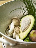 Avocado, mushrooms, figs and chives in a colander