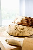 Wheat and rye dough with a baking basket and a rolling pin