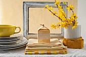 Gestapelte weiße Teller, gelbe Tasse und Tischwäsche, Forsythienzweige in Vase