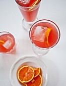 Glasses of blood orange lemonade with citrus slices and ice cubes (seen from above)