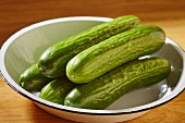 Whole fresh Asian cucumbers in an enamel bowl