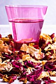 A close-up of a glass of rose water and dried rose petals