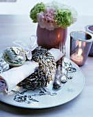 Christmassy place setting with festive napkin ring, ribbon and silver cutlery