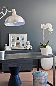 Schreibtisch aus Metall mit einer Orchidee vor grauer Wand
