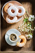 Espresso, doughnuts with icing sugar and flowers on a wooden tray