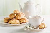 Kaffee und Croissant auf einem weissen Tisch