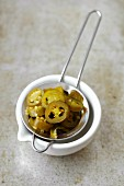Pickled jalapeños in a sieve