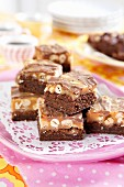 Sliced of chocolate tray bake cake with hazelnuts and caramel