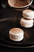Gluten-free macarons being sprinkled with cinnamon