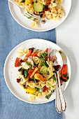 Pasta salad with ham, grilled vegetables and dried tomatoes
