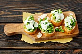 Bruschetta topped with green peas and Parmesan cheese