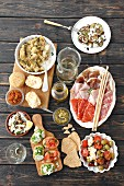 A selection of antipasti (artichokes, arancini, a cold cuts platter, courgette, pesto, bruschetta, seafood salad, tomato and mozzarella salad, Italy)
