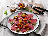 Beef carpaccio with a peperonata dressing and moringa powder