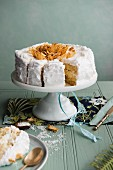 A whole coconut and pinapple cake on a cake stand, sliced