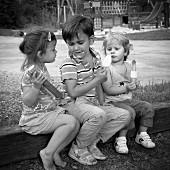 Drei Kinder auf dem Spielplatz essen Eis (s/w-Bild)