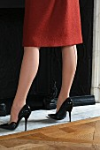 Frau in rotem Wollkleid und Lackpumps trägt Strumpfhose mit Ziernaht