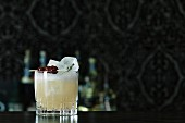 A Whiskey Sour cocktail on a bar