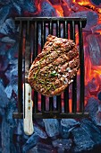 A peppered steak on a cooking grid