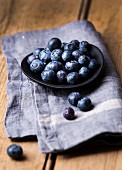 Blueberries in a shallow black bowl on a blue linen cloth