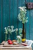 Bread with herb butter and tomatoes next to white flowers in front of an old wooden door