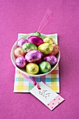 Chocolate Easter eggs in coloured foil in a bowl with a gift tag