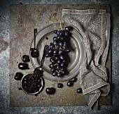 An arrangement of grapes, black cherries and cherry jam
