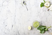A green smoothie in a glass with ingredients