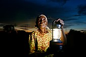 Woman holding a solar powered lamp,Kenya