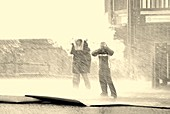 Two people standing in a rainstorm
