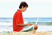 Boy using a laptop at a beach