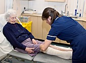 Nurse dressing a patient's leg