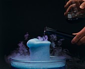 Pouring coloured fluid into a beaker