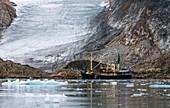Tourist boat dwarfed by glacier terminus