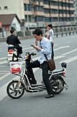Man on a battery-powered moped smoking