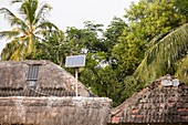 A mud hut with a small solar panel