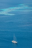 Yacht with coral reef behind