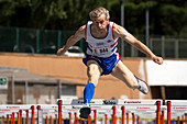 Masters British athlete clearing hurdle