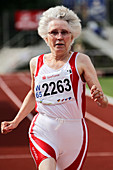 Older female athlete runs to camera