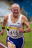 Senior male athlete runs through the pain
